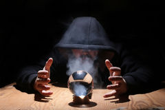Man in a black hood with cristal ball. Summon evil stock image
