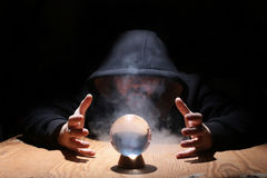 Man in a black hood with cristal ball. Summon evil royalty free stock images