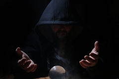 Man in a black hood with cristal ball. Summon evil stock photos