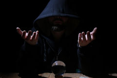 Man in a black hood with cristal ball. Summon evil royalty free stock photo