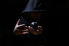 Man in a black hood with cristal ball. Summon evil stock photo