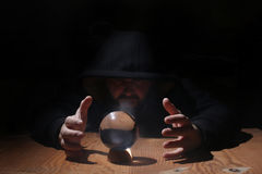 Man in a black hood with cristal ball. Summon evil royalty free stock photography