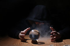 Man in a black hood with cristal ball. Summon evil stock images