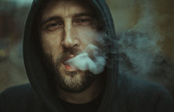 Man in Black Hoodie Jacket Blowing a Smoke Royalty Free Stock Photography