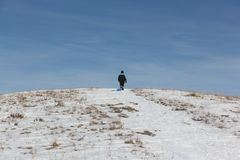Man in a black jacket climbing a mountain with a plastic sled. In winter, Russia, Bugotak Hills Stock Photos