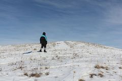 Man in a black jacket climbing a mountain with a plastic sled. In winter, Russia, Bugotak Hills Stock Photography