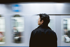 Man in Black Jacket in Front of Train Royalty Free Stock Photography
