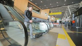 Man in black jacket goes down airport escalator. Young man in black leather jacket with drink in hand goes down airport escalator and walks along hall stock video