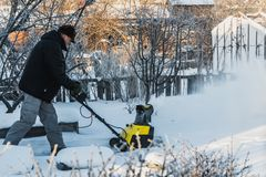 A man in a black jacket and a gray pants is brushing white snow with the yellow electric snow thrower in winter stock photography