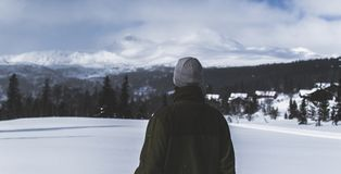 Man With Black Jacket and Grey Knit Cap Standing on White Snow Field stock image