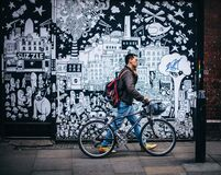 Man in Black Jacket Holding a Black Hardtail Bike Near Black and White Art Wall Stock Image