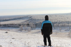 The man in a black jacket with a hood standing on hill top Royalty Free Stock Images