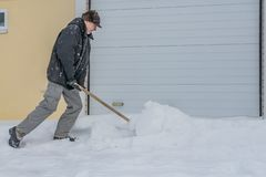 A man in a black jacket and light-colored gray pants and a brown hat cleans snow with a wooden shovel in winter. A man in a black jacket and light-colored gray royalty free stock image