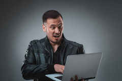 Man in black jacket looking at laptop, half turn. Holding opened laptop and working. Emotion. Royalty Free Stock Photo