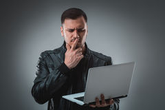 Man in black jacket looking at laptop, half turn. Holding opened laptop and working. Emotion. Stock Image