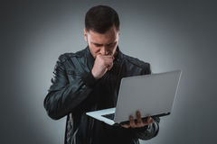 Man in black jacket looking at laptop, half turn. Holding opened laptop and working. Emotion. Stock Photography