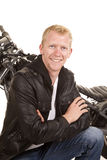 Man in black jacket motorcycle behind him smiling Royalty Free Stock Photography