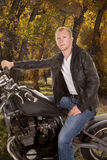 Man in black jacket motorcycle one hand on handlebars looking tr Stock Photo
