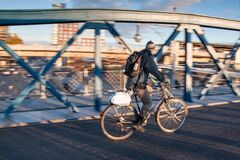 Man in Black Jacket Riding Black Bicycle in Gray Concrete Road in Panning Photography Royalty Free Stock Images