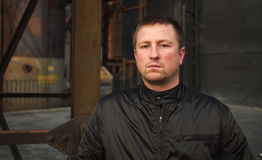 Man in black jacket with serious expression. And dark industrial background stock photography