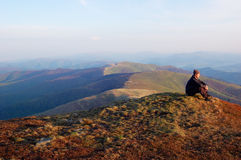 Man sitting on top of a mountain. Man in black jacket sitting on top of a mountain and looks into the distance royalty free stock photo