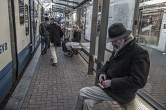 Man in Black Jacket Sitting at the Train Station Stock Photo