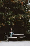 Man in Black Jacket Sitting on White Picnic Table Beside Black Cruiser Bike Under Green Leafed Tree during Daytime Stock Image