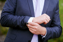 Man in black jacket wears cuffs in park Royalty Free Stock Photo