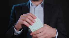 A Man in Black Jacket and White Shirt Holding Cash. A man wearing a black jacket and a white shirt holding cash Euros against a black background. Close-up shot Stock Photos