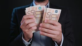 A Man in Black Jacket and White Shirt Holding Cash. A man wearing a black jacket and a white shirt holding cash Euros against a black background. Close-up shot Royalty Free Stock Images