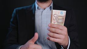 A Man in Black Jacket and White Shirt Holding Cash. A man wearing a black jacket and a white shirt holding cash Euros against a black background. Close-up shot Royalty Free Stock Photo