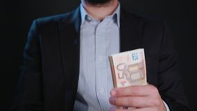 A Man in Black Jacket and White Shirt Holding Cash. A man wearing a black jacket and a white shirt holding cash Euros against a black background. Close-up shot Royalty Free Stock Photos