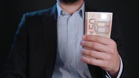 A Man in Black Jacket and White Shirt Holding Cash. A man wearing a black jacket and a white shirt holding cash Euros against a black background. Close-up shot Stock Photo