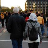 Man in Black Jacket Beside Woman in Grey Leather Jacket Holding Hands at Dusk in Busy Street Stock Photo