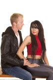 Man in black jacket woman red top sit together Stock Photo