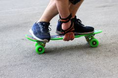 A man in blue sneakers riding a green skateboard royalty free stock photography
