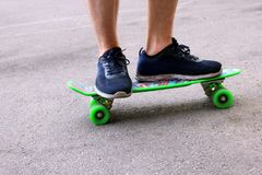 A man in blue sneakers riding a green skateboard stock images