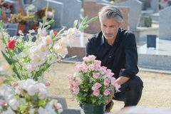 Man in black knelt at grave. Man Stock Photography