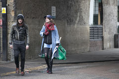A man in a black leather jacket and a girl in ragged pantyhose walking down the street in rainy cold weather. LONDON, ENGLAND - March 12, 2017 A man in a black stock image