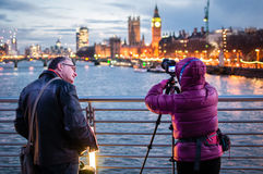 Man in Black Leather Jacket Beside Person in Purple Bubble Jacket Holding Dslr Camera on Tripod Near Body of Water Taking Shot on  Stock Images