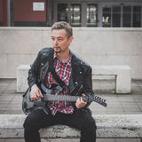 Man in black leather jacket playing electric guitar. On a bench Stock Image