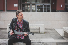 Man in black leather jacket playing electric guitar. On a bench Royalty Free Stock Images
