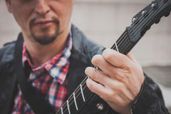 Man in black leather jacket playing electric guitar. In the street Stock Photo