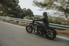 Man in black leather jacket riding a motorcycle on the road across the mountain. Biker riding motor bike with black leather clothes in the road royalty free stock image