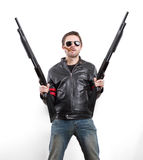 Man in black leather jacket and sunglasses with two shotguns Stock Images