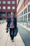Man in black leather jacket walking with electric guitar Stock Photos