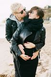 Man in Black Leather Zip Jacket Hugging Woman in Black Leather Zip Jacket and Black Pants Standing on Sand at Daytime stock image