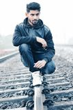 Man in Black Leather Zip-up Hoodie and Black Denim Jeans Sitting on Grey Metal Train Railings Surrounded With Rocks during Husky M Royalty Free Stock Photo