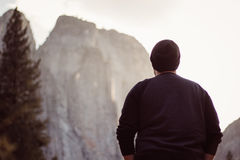 Man in Black Long Sleeve Shirt and Black Knit Cap Facing the Pine Tree and Gray Rocky Mountain Stock Photography