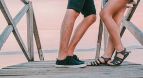 Man in Black Low-top Sneakers Leaning Towards Woman in Black Gladiator Flat Sandals on Dock Royalty Free Stock Photos